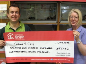 Pets at Home manager David Rear presenting the fundraising cheque to a volunteer